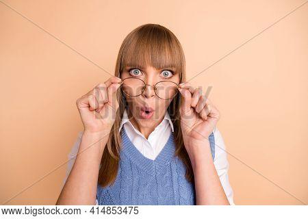 Photo Portrait Of Female Student Amazed Shocked Taking Off Eyewear Whistle Isolated On Pastel Beige