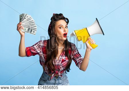 Pretty Pin Up Woman Holding Fan Of Money And Shouting Into Megaphone On Blue Studio Background