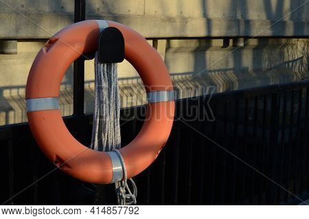 A Bright Orange Life Preserver Is Attached To The Side Of A Water Dam Bridge Located At Old Slys Loc