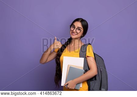 Happy Indian Student Wearing Eyeglasses Holding Notebooks Showing Thumbs Up