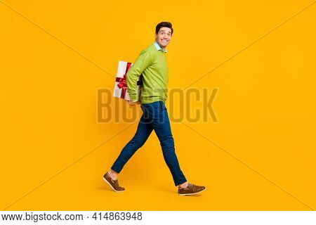 Full Length Body Size Profile Side View Of Nice Funky Cheerful Guy Carrying Hiding Giftbox Isolated