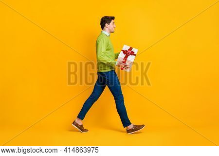 Full Length Body Size Profile Side View Of Cheerful Guy Carrying Holding In Hands Giftbox Greetings