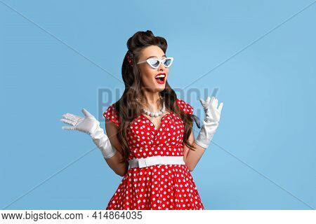Stylish Pin Up Woman In Polka Dot Red Dress And Sunglasses Feeling Excited, Opening Mouth In Shock O