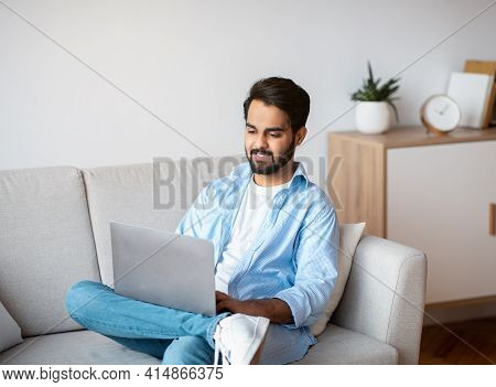 Eastern Millennial Male Using Laptop While Relaxing On Couch At Home