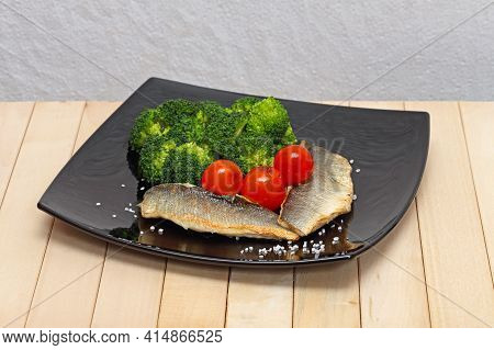 Grilled Fish Fillets With Broccoli Cherry Tomatoes Served At Black Plate