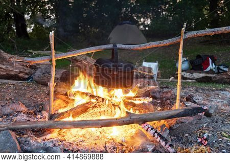 A Saucepan Hanging Over The Fire. Picnic With Barbecue. Evening Bonfire And Tourist Tent. Tent In Th