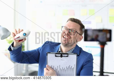 Business Coach Launching Toy Rocket In Front Of Mobile Phone Camera