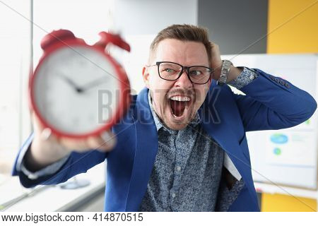 Businessman In Glasses Holding Red Alarm Clock In His Hands And Shouting