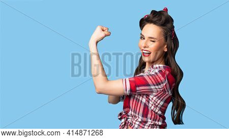 Pretty Pin Up Lady In Retro Style Outfit Showing Her Strength On Blue Studio Background, Banner Desi