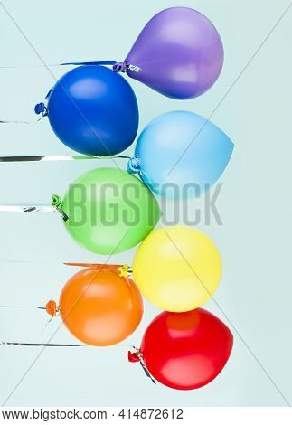 Small Inflatable Balls Of Rainbow Colors Hang On A Ribbon. Holiday Content