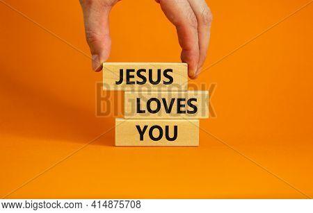 Jesus Loves You Symbol. Concept Words 'jesus Loves You' On Wooden Blocks On A Beautiful Orange Backg