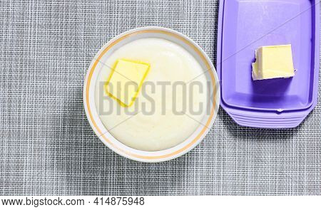 Semolina Porridge In A Plate With Butter And A Piece Of Butter In A Butter Dish Next To It. Top View