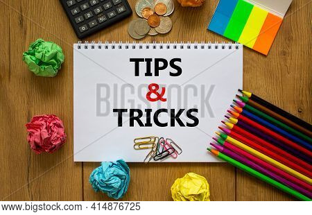Tips And Tricks Symbol. White Note With Words 'tips And Tricks' On Beautiful Wooden Table, Colored P