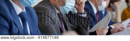 Businessmen Or Officials In Formal Suits With Ties Sit With Documents During A Meeting Or Formal Neg