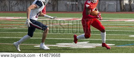 Wide Receiver Running Away From Defender Who Is Trying To Tackle Him During A High School Football G