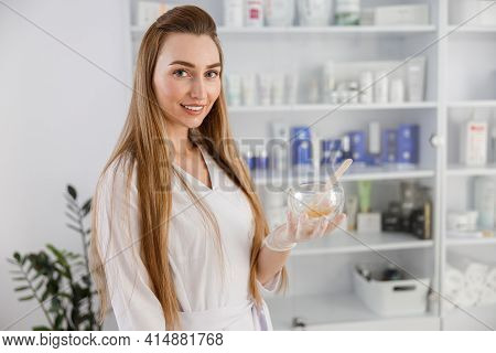 Female Beautician Holds Jar With Wooden Spatula. Woman Beautician Doctor At Work In Spa Center