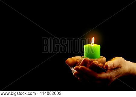 Hands Hold Green Burning Candle In The Dark.