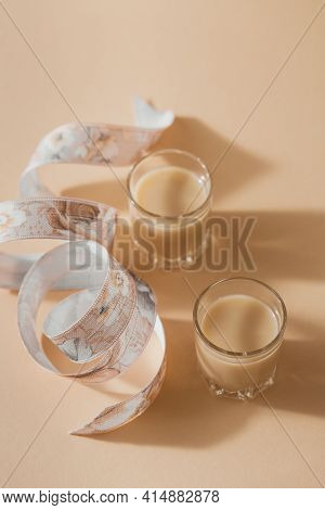 Short Glasses Of Irish Cream Liquor Or Coffee Liqueur With Ribbon On Light Beige Background