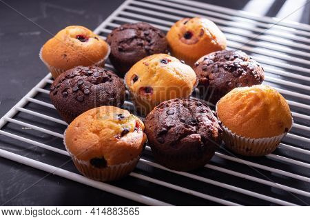 Lots Of Different Muffins On The Kitchen Grill. Chocolate And Milk Muffins.