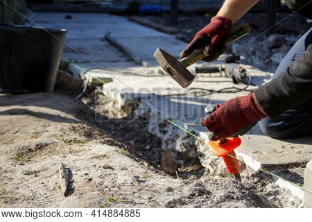 Defocus Construction Worker. Male Hands In Red Work Gloves Hold A Hammer And Chisel. The Paver Paver