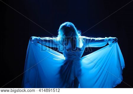 Attractive Plus Size Model Posing On Dark Background In The Rays Of Lights.
