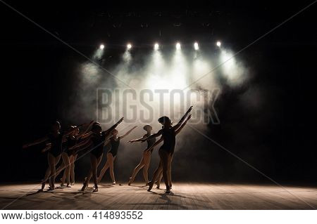 Ballet Class On The Stage Of The Theater With Light And Smoke. Children Are Engaged In Classical Exe