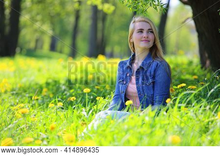Beautiful Young Woman Sitting In Spring Park With Dandelion Flowers