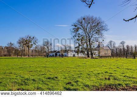 Uncultivated Dutch Farm Field With Green Grass, Trees With Sparse Foliage With Genhoes Castle In The