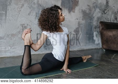 Yoga Trainer In Sportswear Doing Splits. Young African American Woman Stretching Legs, Make Daily Sp