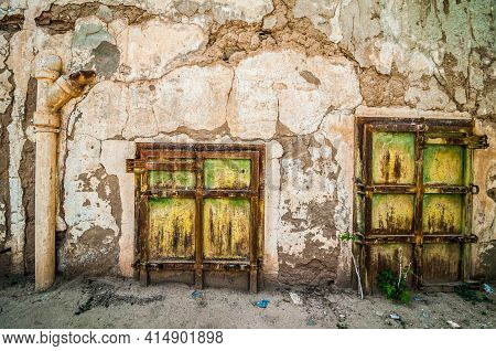 Aouli, Morocco - April 10, 2015. Green Rusty Doors Of Abandoned House, Partly Buried By Sand