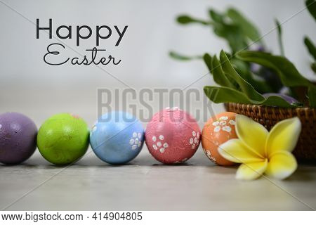 Happy Easter. With Easter Eggs Lined Up Horizontally, A Yellow Flower And A Basket With Leaves Decor