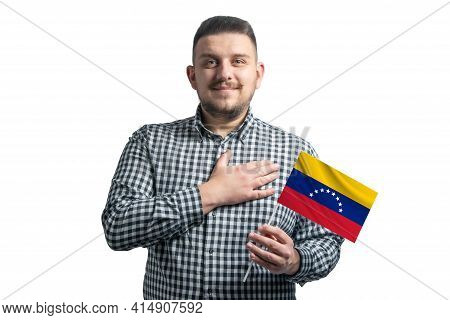 White Guy Holding A Flag Of Venezuela And Holds His Hand On His Heart Isolated On A White Background