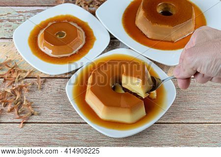 Man Taking A Slice With A Spoon Of Condensed Milk Pudding With Caramel Sauce, Alongside Other Puddin