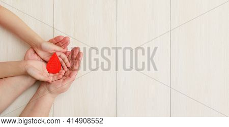Hands Of The Mother And Child Hold Drop Of Blood On A White Background.concept Of Give Blood Donatio