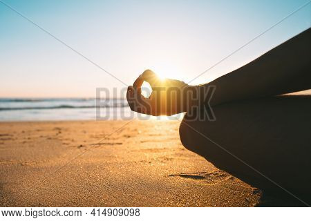 Meditating On The Beach At Sunrise In The Morning. Sitting On The Sand In Easy Pose Or Sukhasana Wit