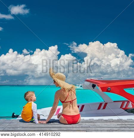 Three year old toddler boy with mother sitting on wooden jetty with boat. Summer family vacation at Maldives.