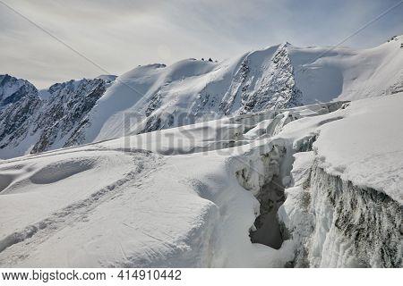 Crevasses split a glacier, in high mountains