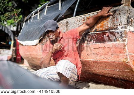 African fisherman on beach repairing his boat