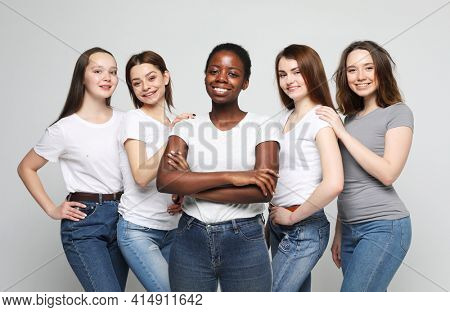 Group of happy young women of different size and ethnicity in t-shirts over grey background