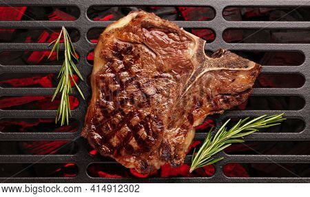 T-bone beef steak cooking on grill. Top view flat lay