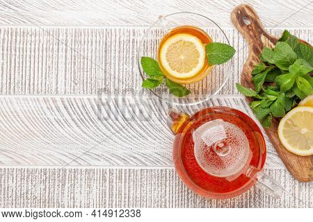 Herbal tea with mint and lemon. Tea cup and teapot on wooden table. Top view flat lay with copy space