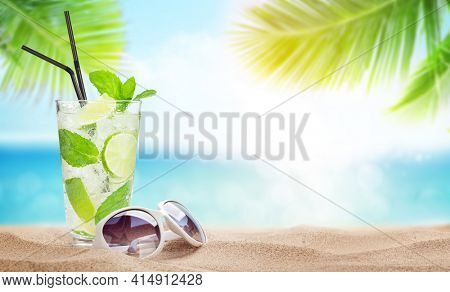 Fresh cold cocktail and sunglasses on tropical beach with palms and bright sand. Summer sea vacation and travel concept with copy space