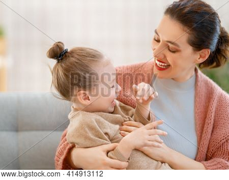 Mom and her daughter child girl are playing, smiling and hugging at home.
