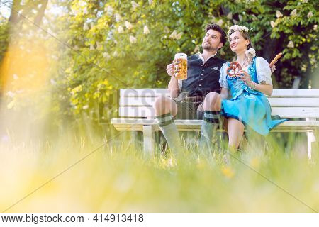 Couple in Bavaria sitting on bench toasting with beer
