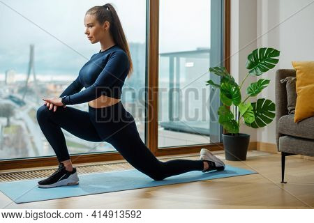 Brunette woman in green tracksuit practices yoga in warrior pose on mat by panoramic window and green pot plant in lodge