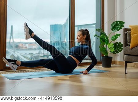 Sportive brunette woman with brown ponytail does stretching legs exercise near panoramic window with view on city in summer