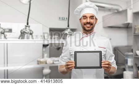 cooking, culinary and people concept - happy smiling male chef in toque showing tablet pc computer over restaurant kitchen background