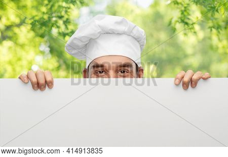 cooking, culinary and people concept - male chef in toque hiding behind big white board over green natural background