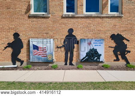 Palatine, IL USA - March 28, 2021: A display on a brick building depicting a memorial for military personnel with a plaque dedicating all who have served in the United States Armed Forces.