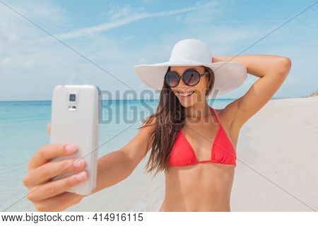 Selfie from bikini young woman travel social media influencer taking photo with mobile phone. Tourist Asian girl using smartphone outside during holidays.